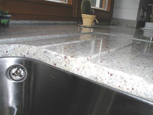 Arbeitsplatte: Kashmir White Oberfläche: poliert Bearbeitung: Abtropffläche mit Wasserstrahl geschnitten und schräg eingeklebt 4 Stück Ablaufrillen eingefräst Ausschnitte: für Unterbaubecken Ecken gerundet, poliert
